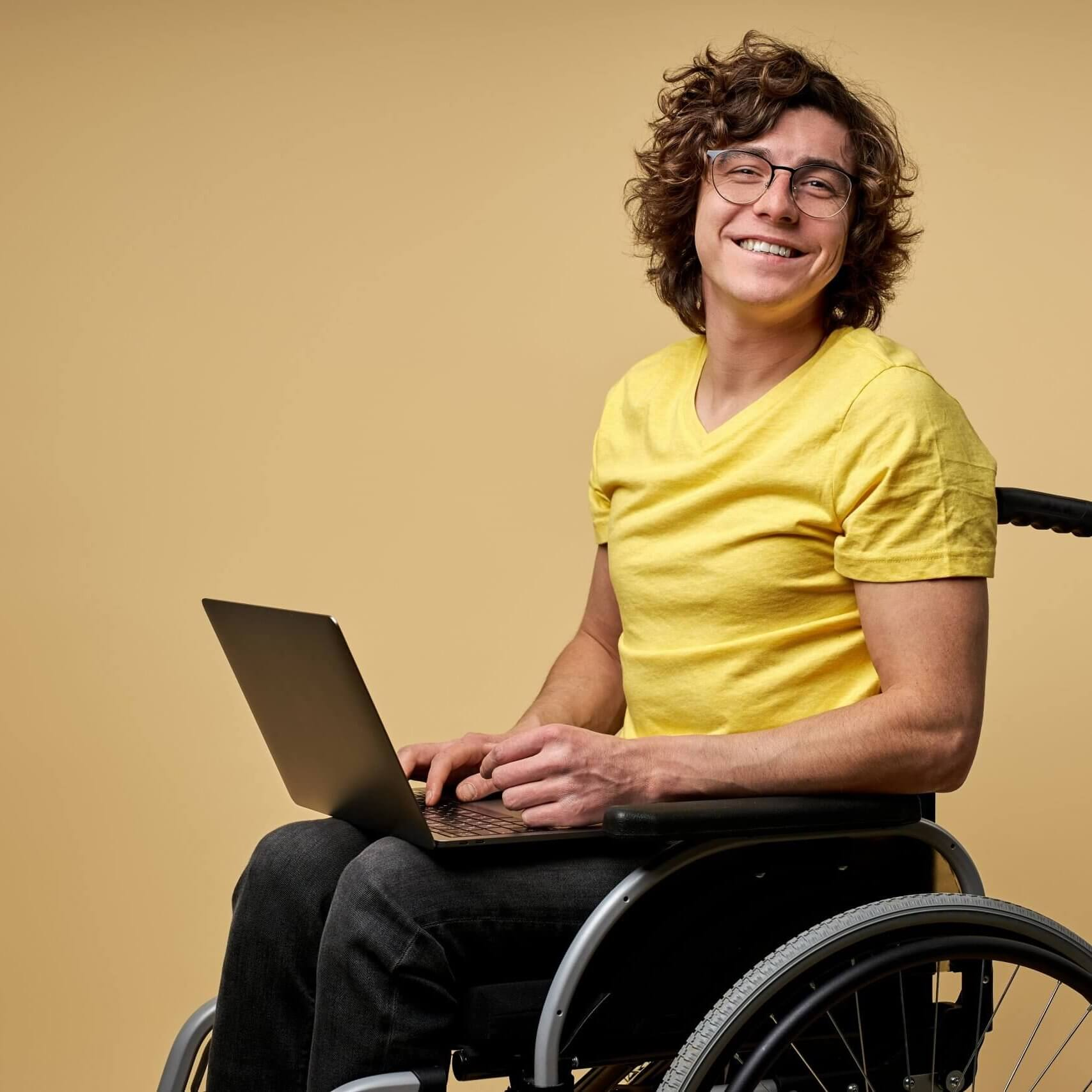 disabled man sits in a wheelchair with laptop, working online. curly young male in casual wear smiles at camera isolated in studio on beige background
