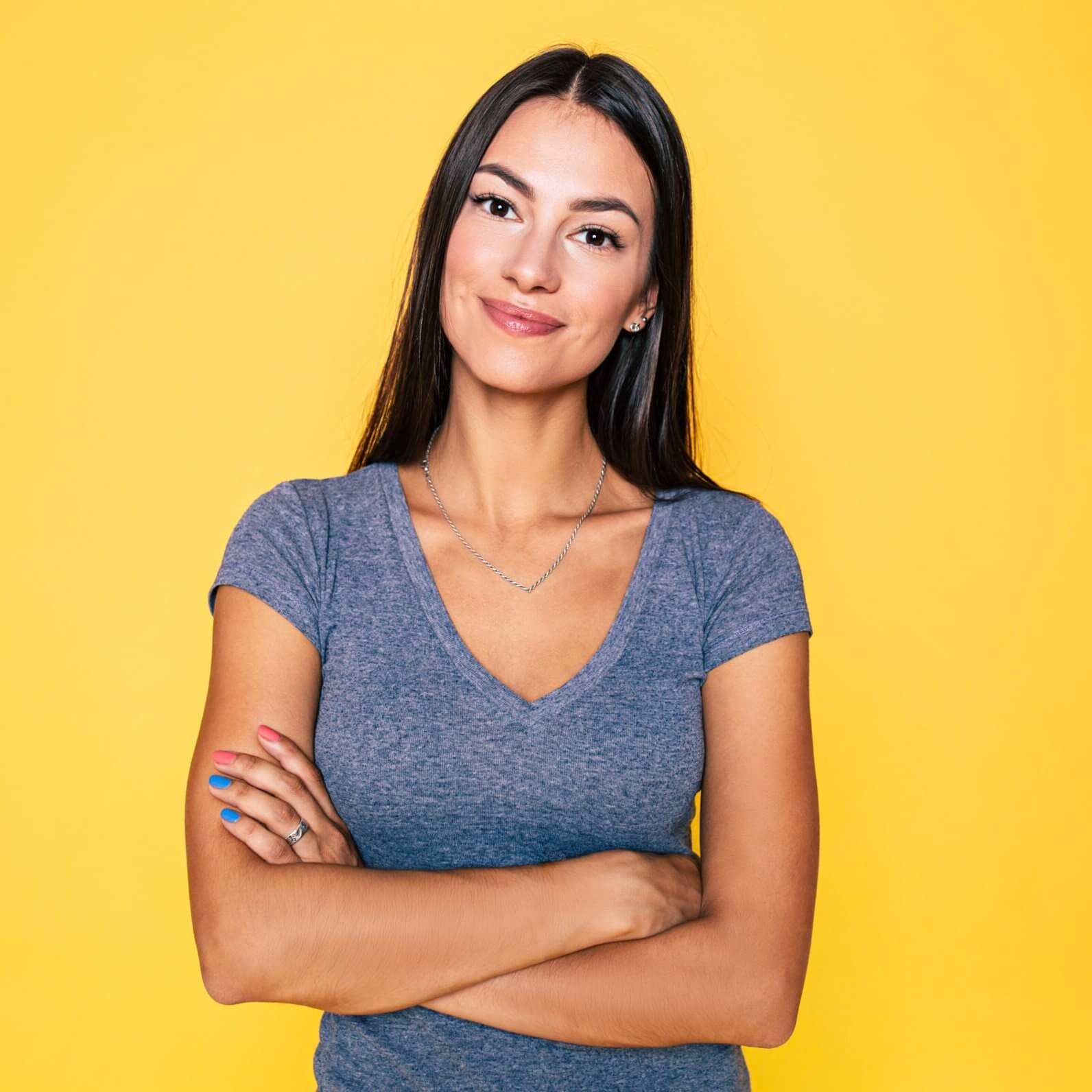 Young attractive cute brunette woman in gray T-shirt is posing and looking on camera isolated over yellow wall
